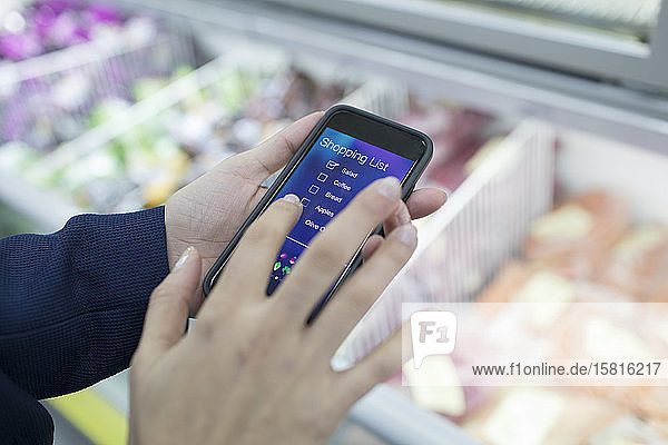 Close up woman using smart phone shopping list app in supermarket