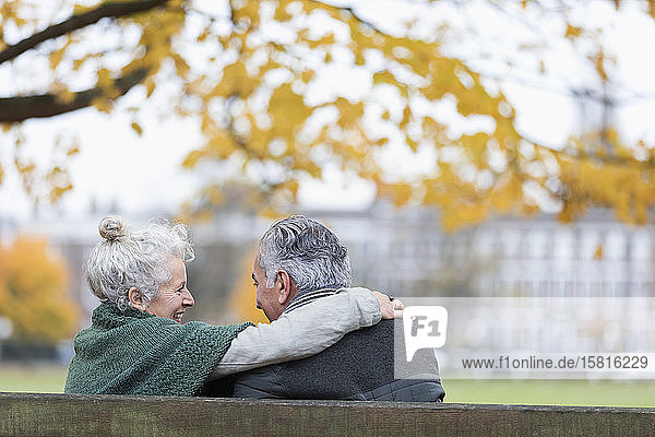 Carefree  affectionate senior couple hugging on bench in autumn park
