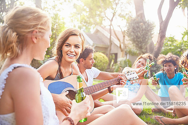 Young women friends hanging out  playing guitar and drinking beer in summer grass