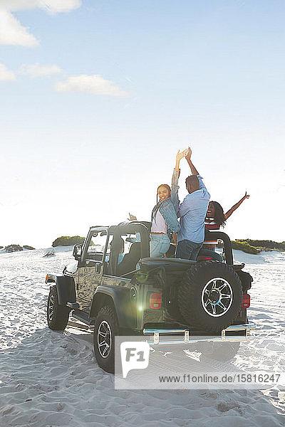 Übermütige junge Freunde,  die mit erhobenen Armen im Jeep am Strand jubeln und einen Road Trip genießen