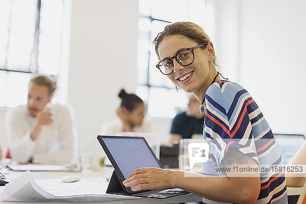Portrait smiling  confident female architect working at laptop in conference room meeting