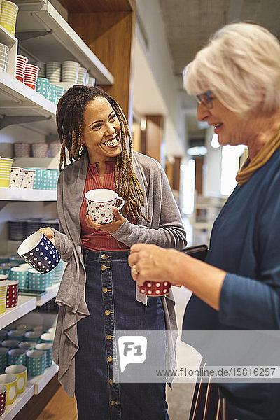Lächelnde Mitarbeiterin hilft einer älteren Frau beim Einkaufen von Tassen