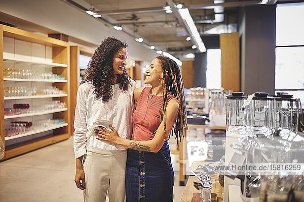 Happy lesbian couple shopping in home decor shop