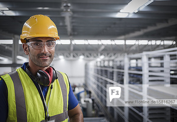 Portrait male worker with ear protectors in factory Portrait male worker with ear protectors in factory