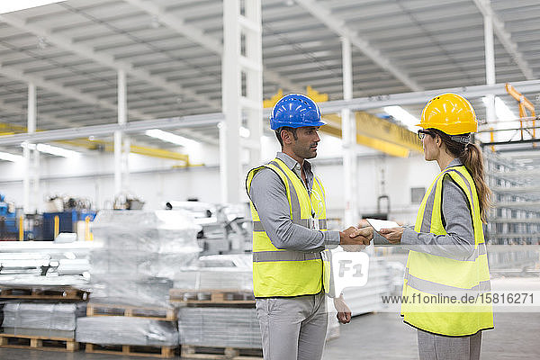 Supervisors handshaking in warehouse