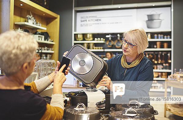 Ältere Frauen mit Smartphone beim Einkaufen in einem Haushaltswarengeschäft