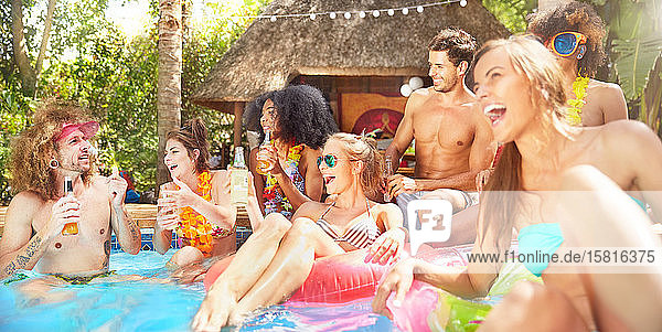 Young friends laughing  hanging out and drinking in sunny summer swimming pool Young friends laughing, hanging out and drinking in sunny summer swimming pool
