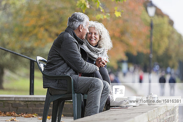 Smiling  affectionate active senior couple drinking tea in autumn park