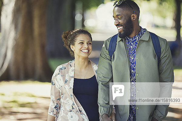Smiling  happy young couple walking in park