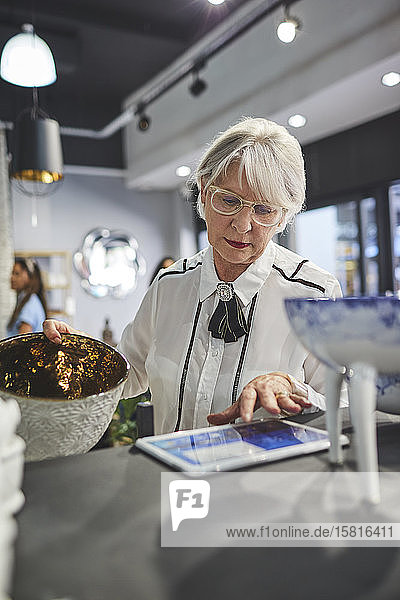 Senior woman with digital tablet working in home decor shop