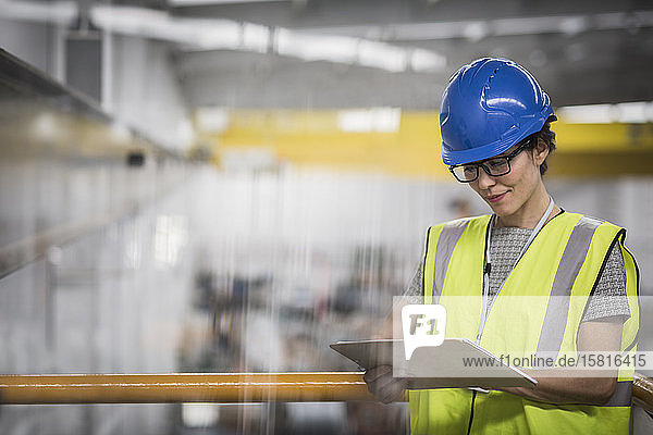 Female supervisor with clipboard on platform in factory