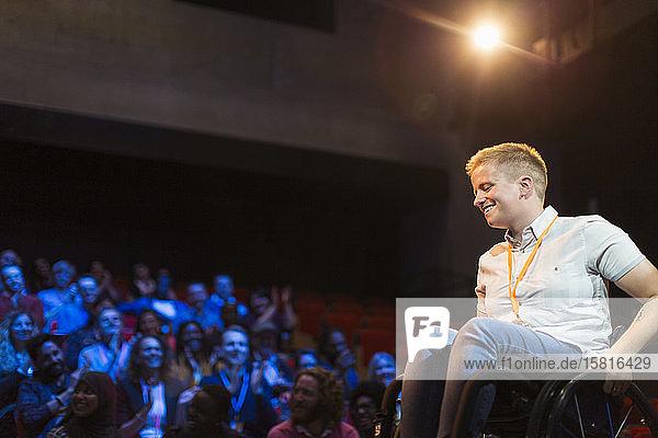 Smiling female speaker in wheelchair on stage Smiling female speaker in wheelchair on stage