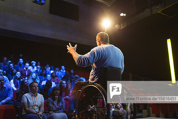 Audience watching male speaker in wheelchair talking on stage