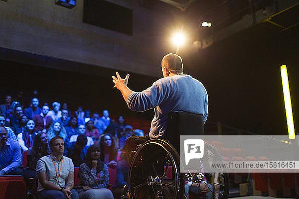 Audience watching male speaker in wheelchair talking on stage Audience watching male speaker in wheelchair talking on stage