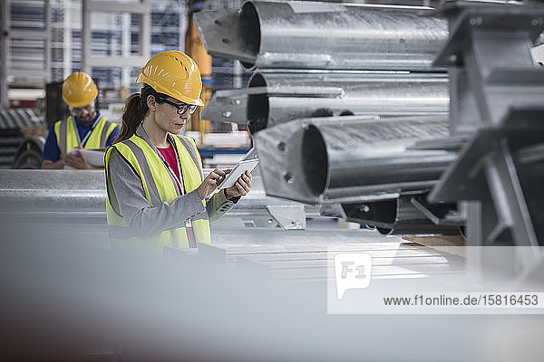 Female supervisor using digital tablet in steel factory