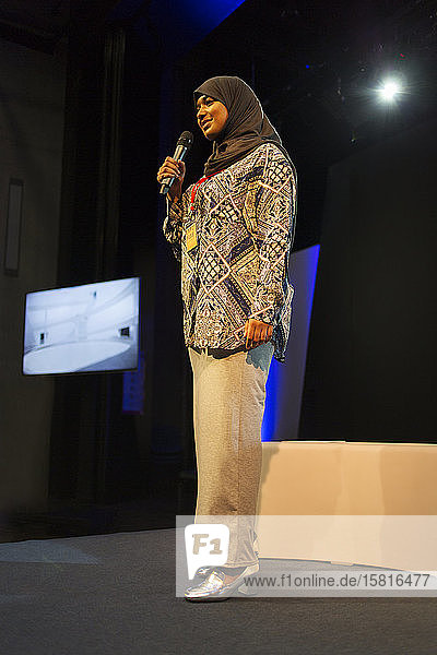 Female speaker in hijab talking with microphone on stage