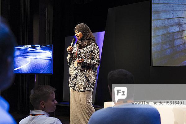 Female speaker in hijab on stage talking to audience Female speaker in hijab on stage talking to audience