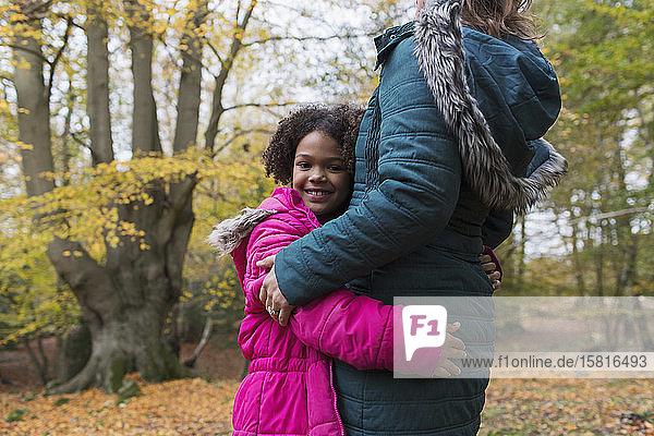 Portrait of happy girl hugging mother in autumn woods Portrait of happy girl hugging mother in autumn woods