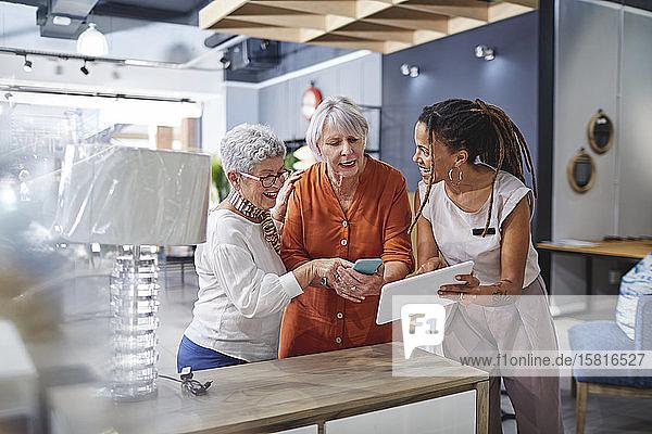 Frau hilft Kunden beim Einkaufen in einem Geschäft für Wohnkultur