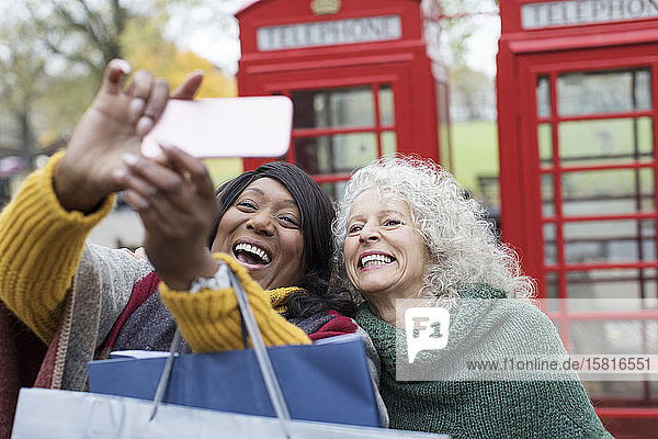 Smiling senior women friends taking selfie in park in front of red telephone booths