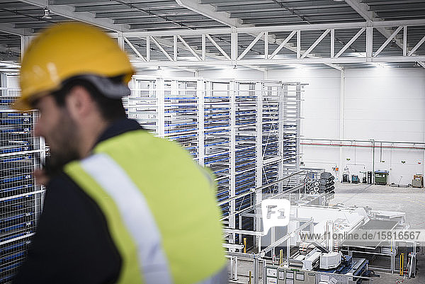 Male supervisor talking  using walkie-talkie on platform in factory Male supervisor talking, using walkie-talkie on platform in factory