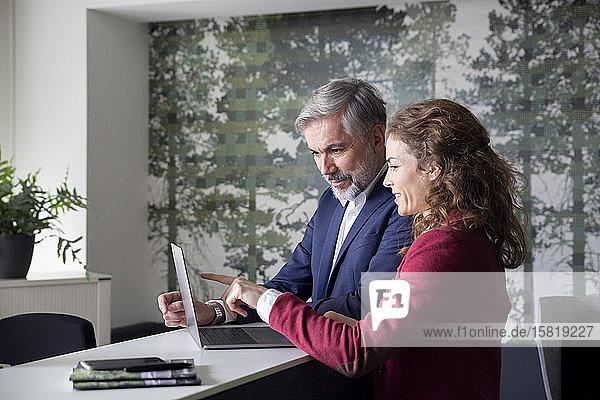 Geschäftsmann und Geschäftsfrau arbeiten gemeinsam am Laptop im Büro