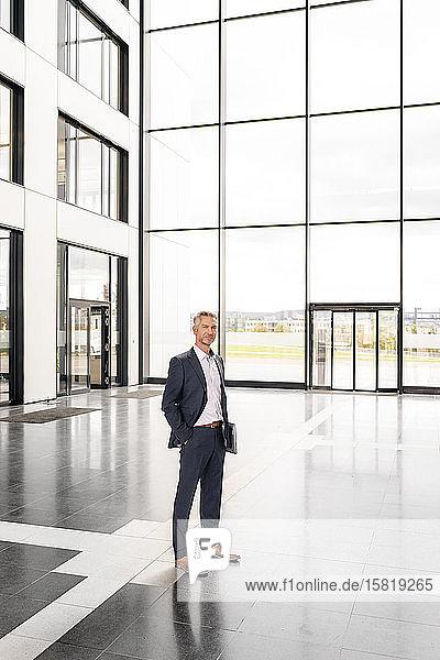 Erfolgreicher Geschäftsmann steht in der Eingangshalle eines Bürogebäudes  mit Händen in den Taschen