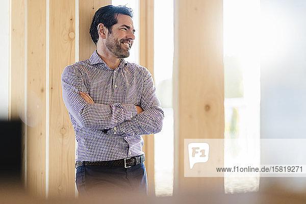 Lächelnder Geschäftsmann im hölzernen Großraumbüro
