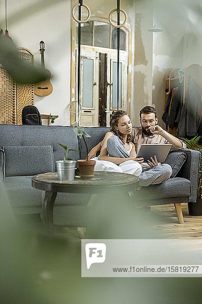 Junges Paar sitzt zu Hause auf dem Sofa und benutzt ein digitales Tablett