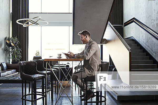 Businessman using tablet in hotel lobby