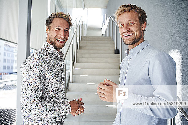 Portrait of two happy young businessmen at staircase