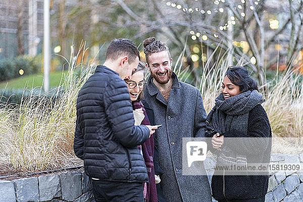 Glückliche Freunde schauen auf Smartphones in der Stadt
