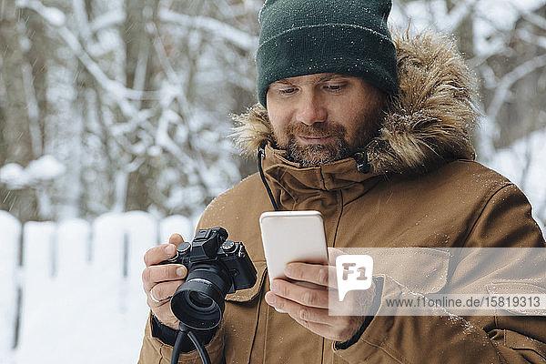 Porträt eines bärtigen Mannes  der mit einer Digitalkamera auf sein Handy schaut  im Winter