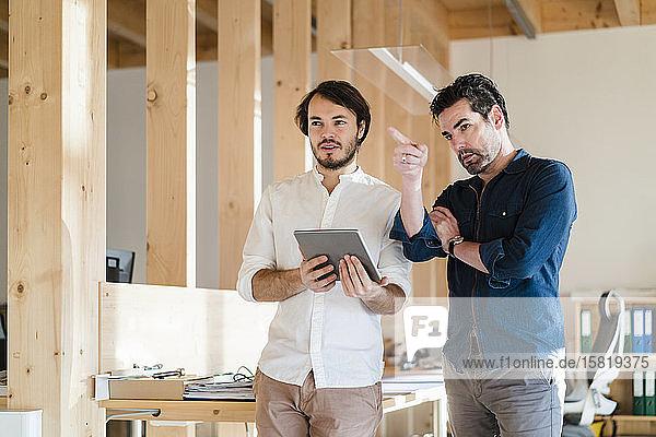 Zwei Geschäftsleute mit Tablett sprechen im hölzernen Großraumbüro