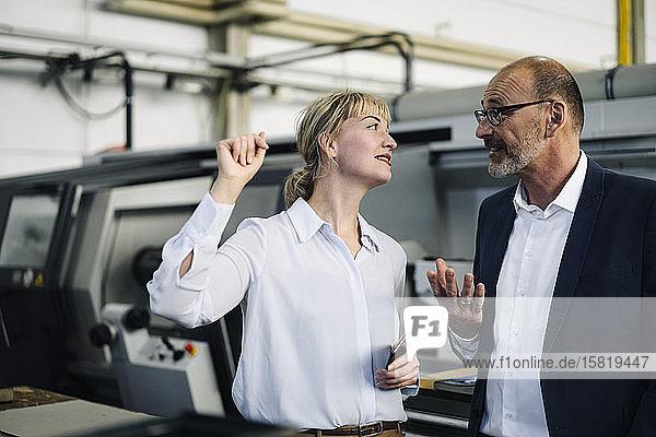 Geschäftsmann und -frau im Gespräch in einer Fabrik