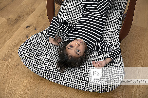 Portrait of little girl lying upside on armchair