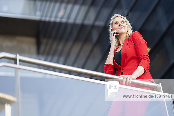 Blond businesswoman wearing red suit and using smartphone