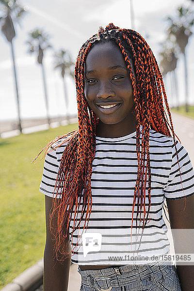 Porträt eines lächelnden Teenager-Mädchens mit Zöpfen im Freien