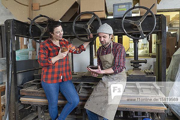 Handwerkerin und Handwerker mit Tablette diskutieren in ihrer Werkstatt