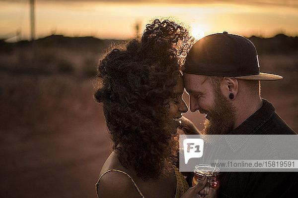 Glückliches Paar trinkt bei Sonnenuntergang im Freien frischen Eistee