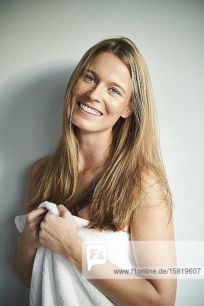Porträt einer glücklichen  in ein Handtuch gewickelten jungen Frau
