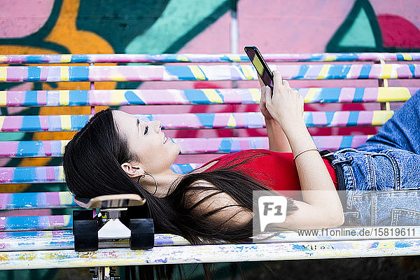 Young woman lying on a bench at skatepark