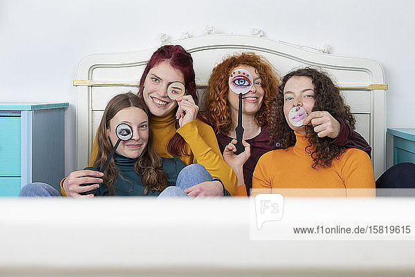 Family portrait of mother and her three daughters sitting together on bed holding paper masks