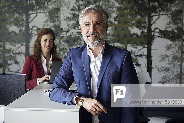 Porrait of smiling businessman in office with businesswoman in background