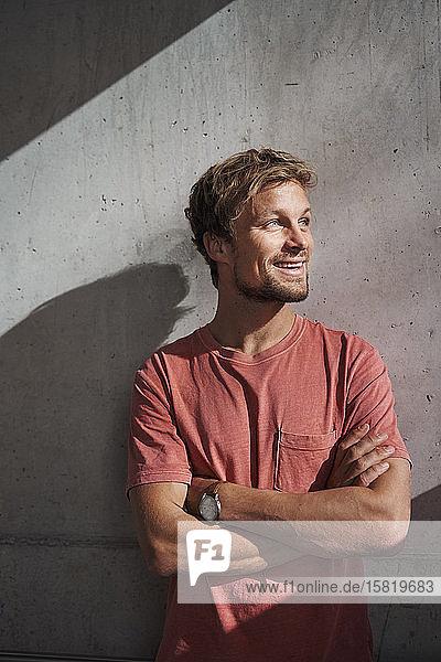 Porträt eines Mannes mit rotem T-Shirt an Betonwand