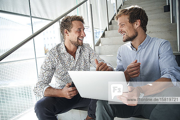 Two happy young businessmen sitting on stairs using laptop
