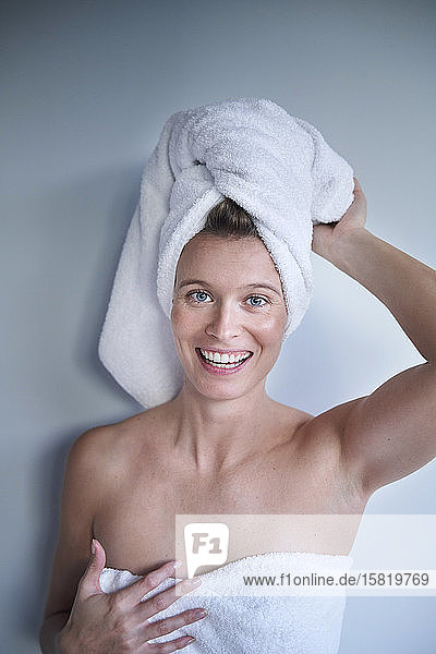 Portrait of happy young woman with her head wrapped in a towel