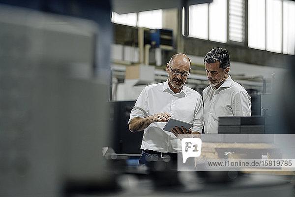 Zwei Geschäftsleute verwenden Tabletten in einer Fabrik