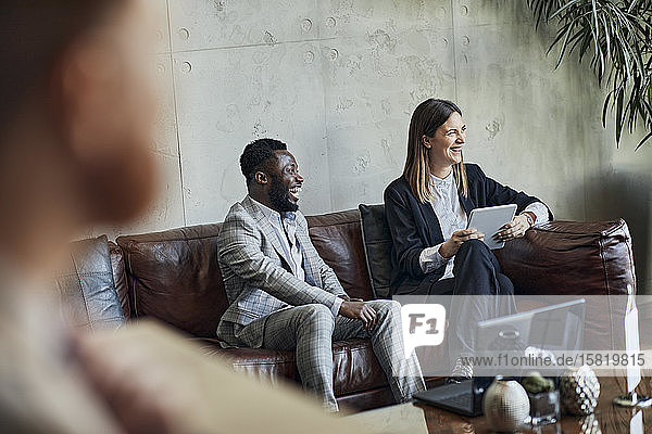 Laughing businessman and businesswoman sitting on couch in hotel lobby during a meeting