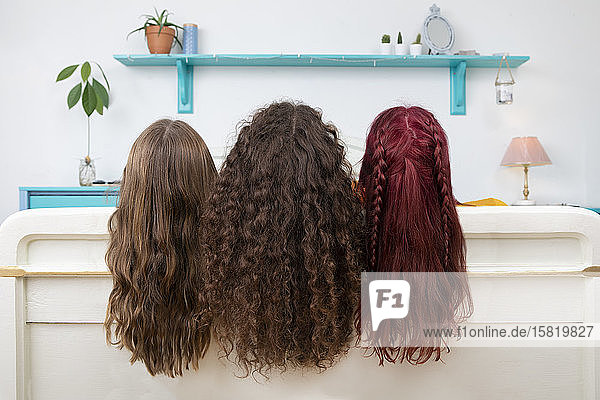 Back view of three sisters with long hair